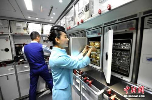 图为空乘在飞机上整理烤箱内的食物。 王东明 摄