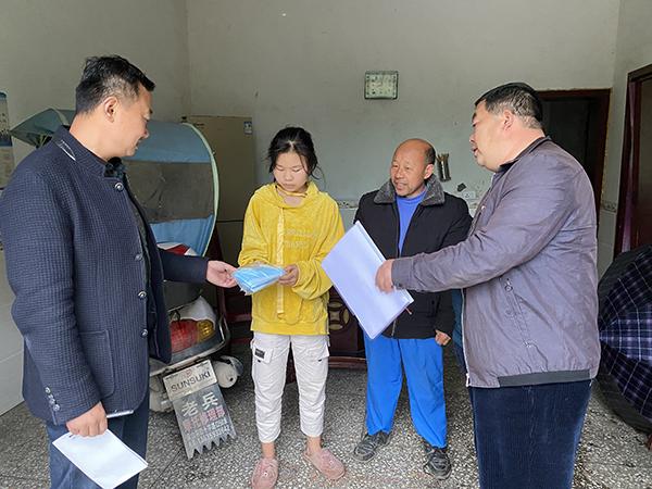 村党支部书记(右一)和第一书记钟鹏翔(左一)走访贫困户陈光全,并为其在读书的女儿送上口罩