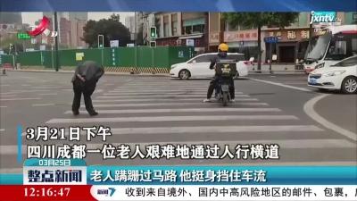 四川:老人蹒跚过马路 他挺身挡住车流