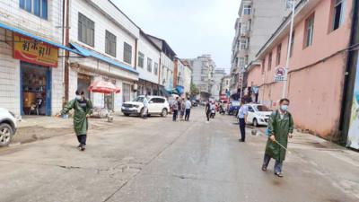 洪水退后,军山集镇数10名环卫人员 对受淹的农贸市场忙清淤消毒